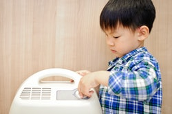 The little boy hand turn off the dehumidifier in the bedroom.