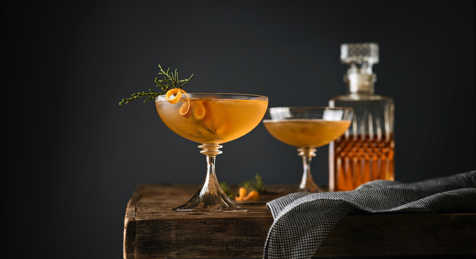 Still life of two Manhattan cocktails garnished with Juniper on a table with whiskey decanter in the...
