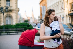 Millennial generation mother with baby in modern red pram walking in downtown on sunny summer day.