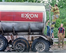 Wilmington fire fighters inspect the Exxon tanker that was involved in an accident with a motorcycle...