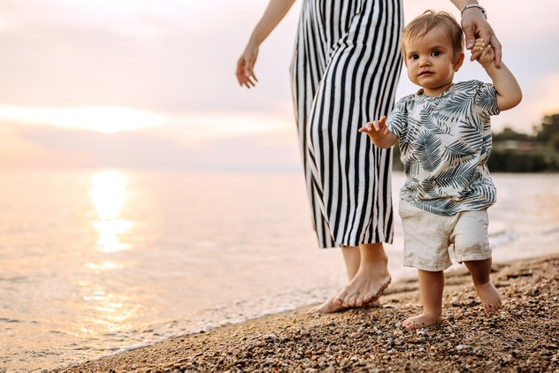 Mother and cute little boy walking at the beach, the mother is unrecognizable