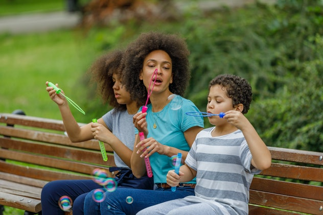 Happy African-American Family is Sitting on a Park Bench and Having a Lot of Fun While Blowing Bubbl...