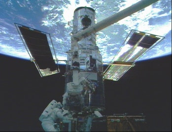 Discovery astronauts Steven Smith, lower left, and Mark Lee work on the Hubble Space Telescope in th...