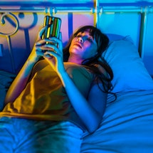 A young woman watches TikTok before bed. Here's how watching TikTok affects your dreams.