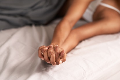 couple in bed holding hands