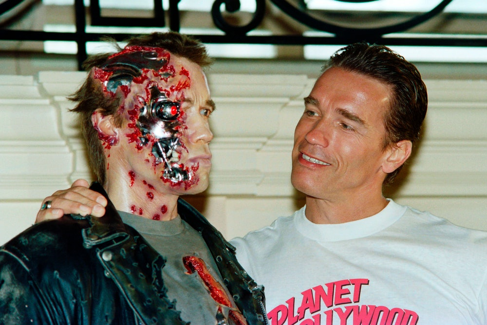 """Us Actor Arnold Schwarzenegger poses next to the wax work of his new shape in the movie """"Terminator ..."""