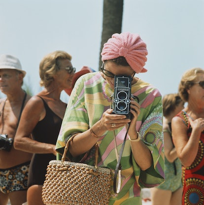 Princess Grace of Monaco taking a photograph at a swimming competition at Monte Carlo.