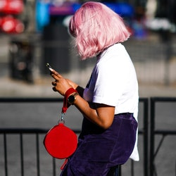 LONDON, ENGLAND - SEPTEMBER 14: A guest wears a white t-shirt, a navy blue skirt, a red circular bag...