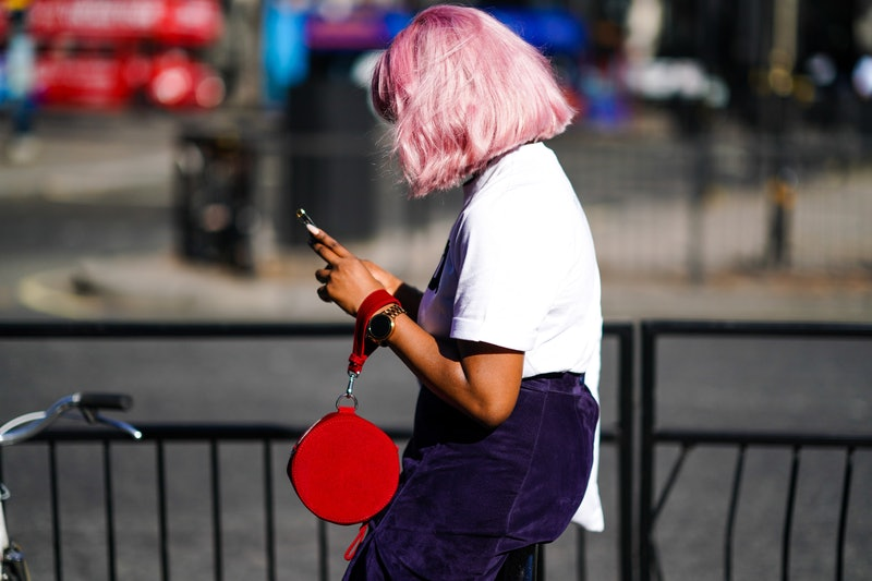 LONDON, ENGLAND - SEPTEMBER 14: A guest wears a white t-shirt, a navy blue skirt, a red circular bag, a watch, during London Fashion Week September 2019 on September 14, 2019 in London, England. (Photo by Edward Berthelot/Getty Images)