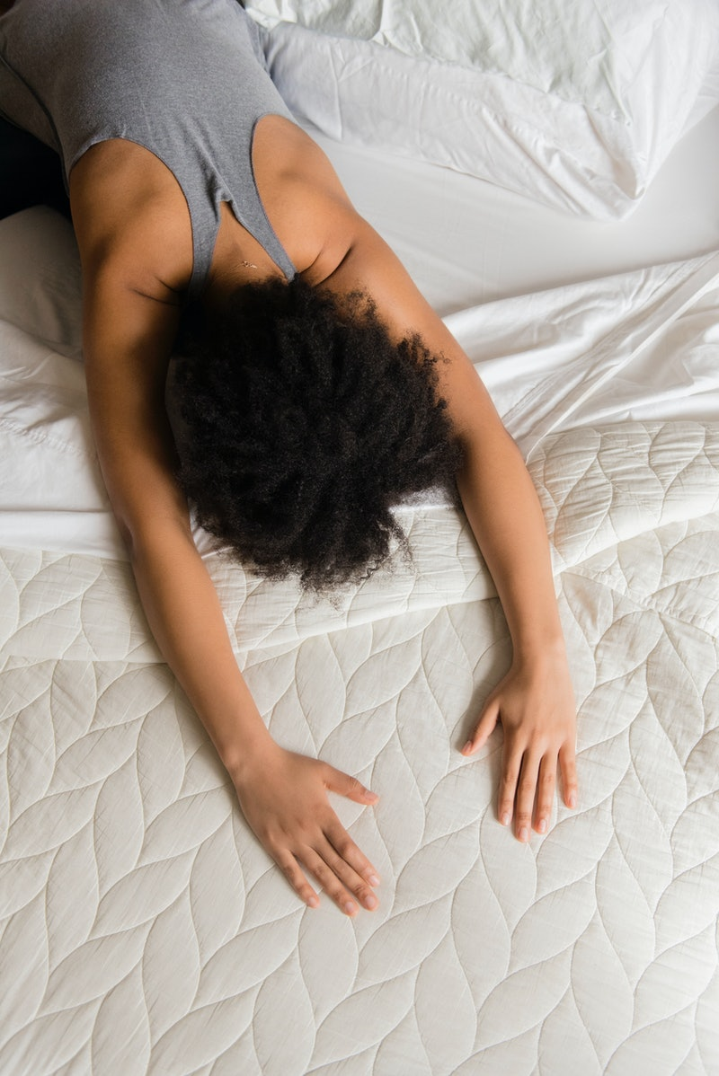 A woman stretches face down in bed, feeling extra tiredness after taking melatonin while on antidepr...