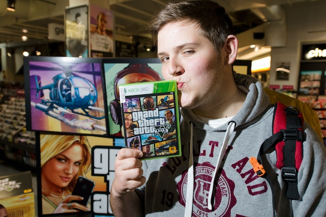 Taylor Pelling of Sutton poses with his copy of the console game Grand Theft Auto 5 at the midnight ...