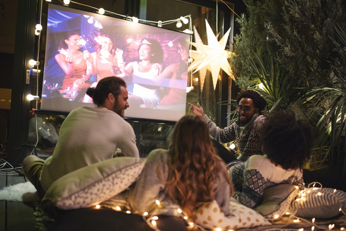 Friends making movie night in their backyard to show what to bring to an outdoor movie.