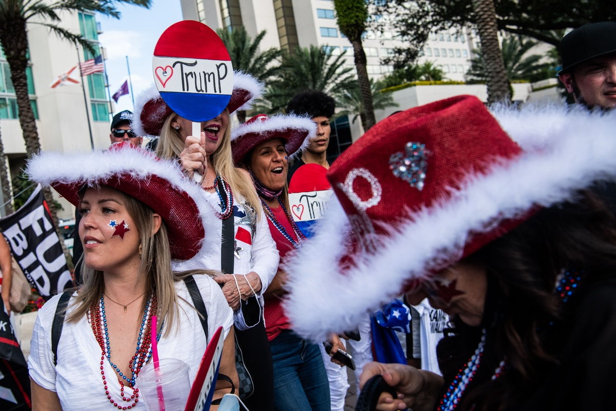 Supporters of former US President Donald Trump cheer for his arrival outside of a hotel where the Co...