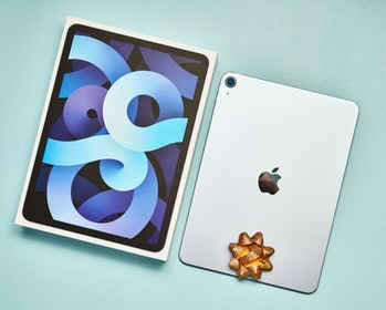 Peyton, Colorado, USA - 26 November 2020: A studio shot of a brand new Apple iPad Air 4 in sky blue with its packaging and a gold bow on a pale blue surface.