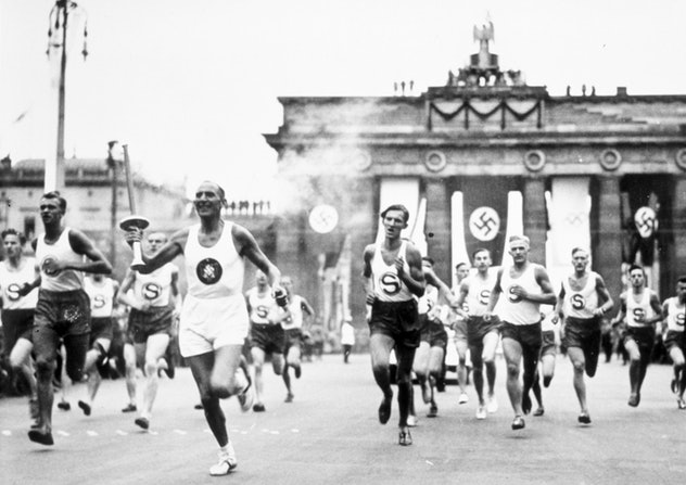1 Aug 1936:  The torch bearer runs through the streets en route to the Olympic Stadium in Berlin, Ge...