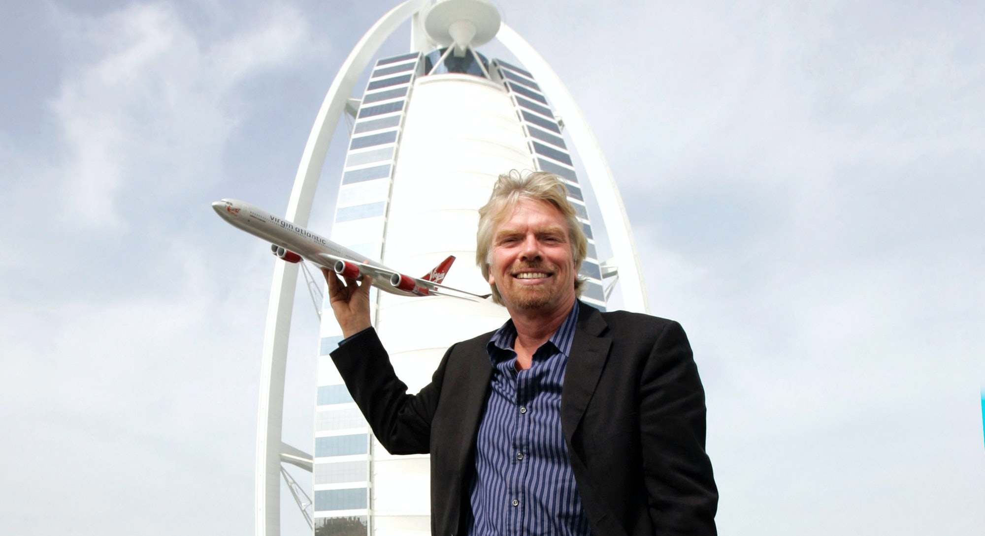 British entrepreneur Sir Richard Branson, who owns Virgin Group, holds a model Virgin airplane in fr...