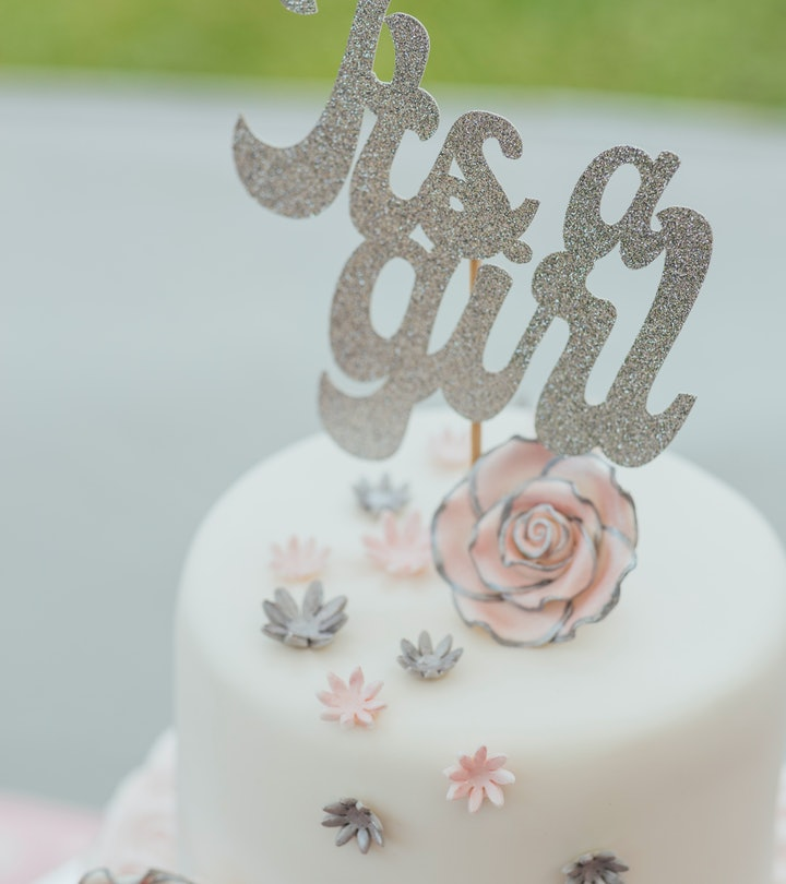 A shot of a two tier cake decorated with flowers and topped with a 'Its a Girl' sign.