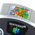 Gothenburg, Sweden - April 30, 2011: A shot of the very popular game Super Mario 64 inserted in a video game console from Nintendo, isolated on white.