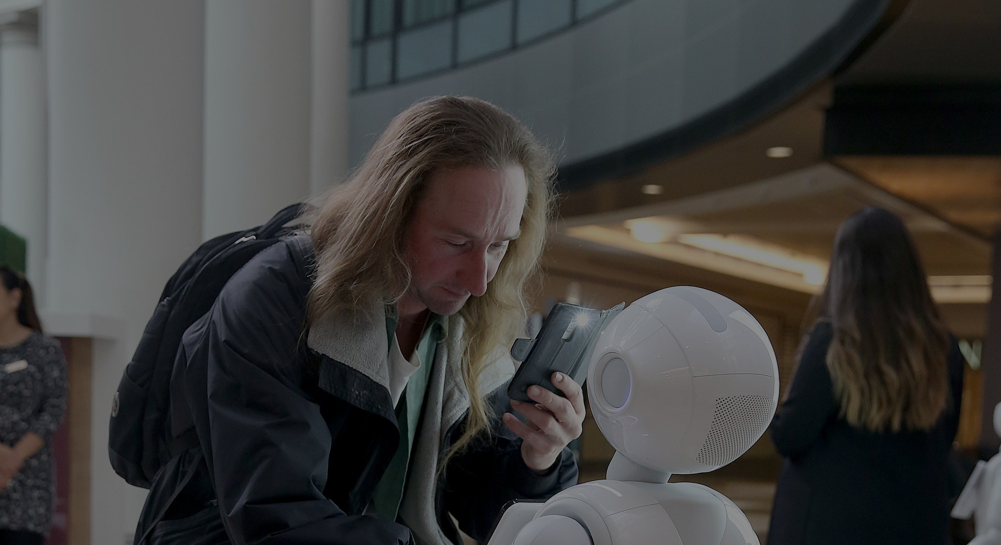 Paul Bartholomew interacts with Pepper, a robot by SoftBank Robotics, which will greet and play game...