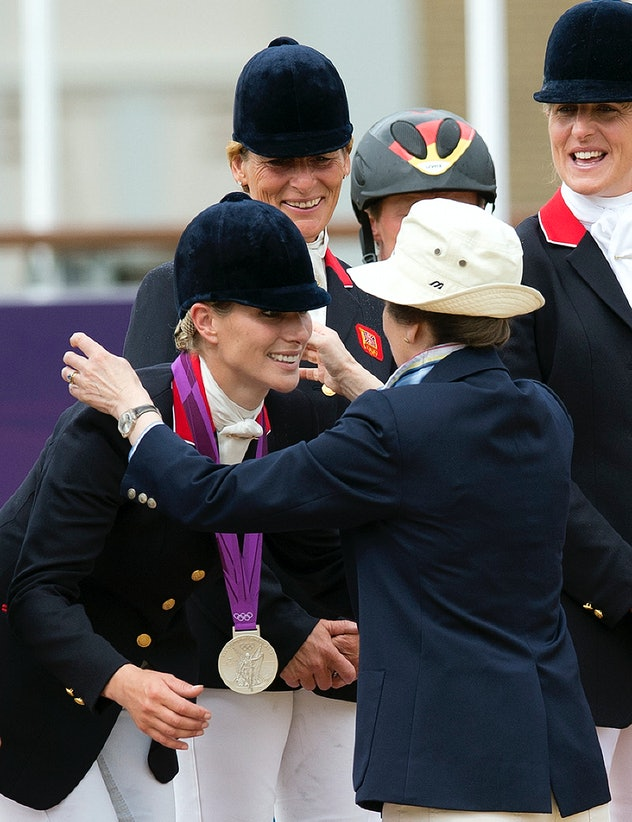 Britain's Zara Phillips (L) receives a silver medal from her mother Princess Anne after she and team...