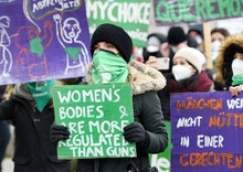 """20 March 2021, Bavaria, Munich: A woman carries a sign reading """"Women's Bodies are more regulated th..."""