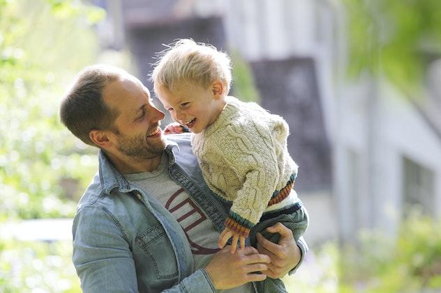 dad holding little boy and laughing