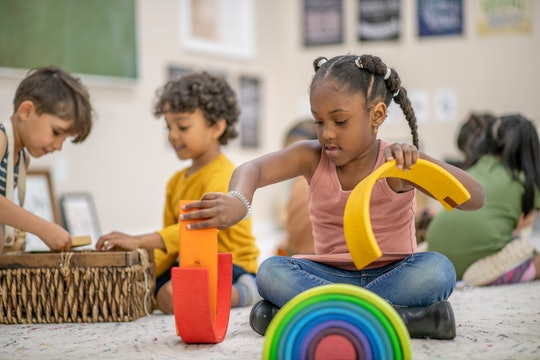 a little girl playing with a rainbow toy in the middle of a preschool classroom