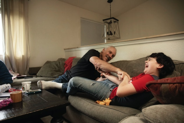 A grandfather play wrestles with his grandson on a couch in a living room.