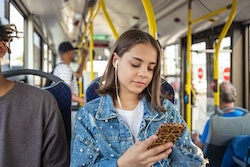 teen girl listening to podcast on bus.