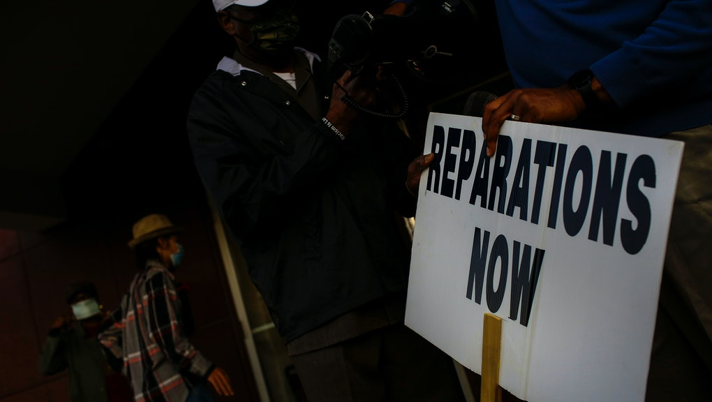 TULSA, OK - NOVEMBER 18: Vernon AME Church pastor Robert Turner holds a reparations now sign after l...