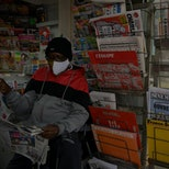 """A newsagent reads the local newspaper """"La Provence"""" in Marseille, as French newspaper distributor co..."""