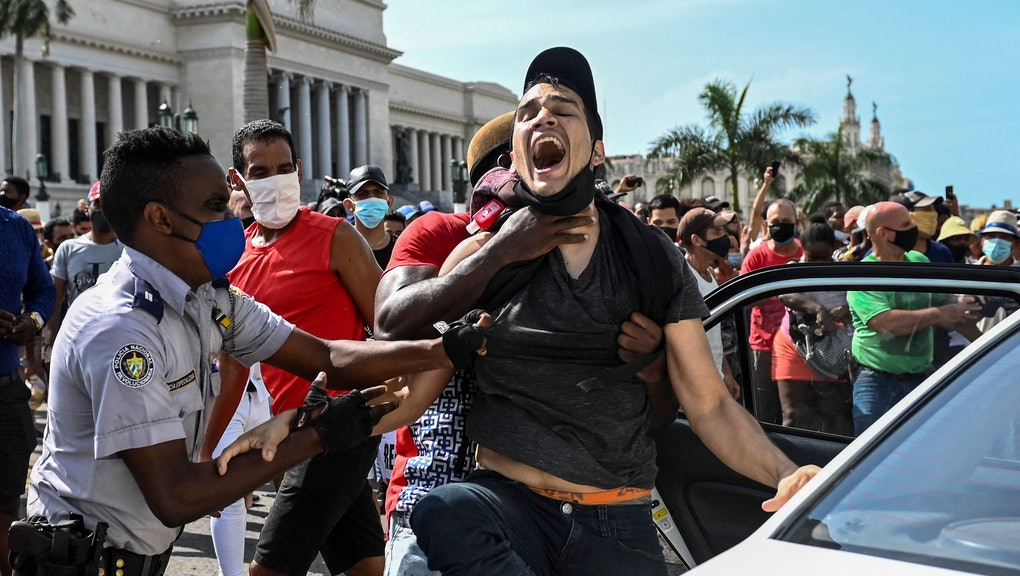 TOPSHOT - A man is arrested during a demonstration against the government of Cuban President Miguel ...