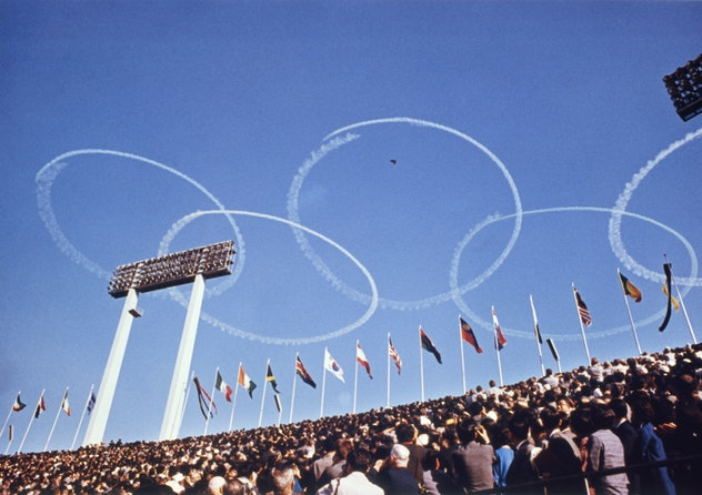 Sky writers trace the Olympic symbols, interlocking rings, in the air above the National stadium on ...