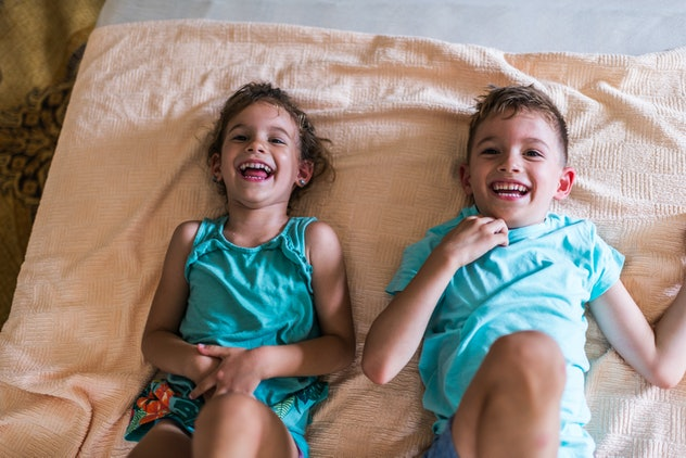 Little boy and his sister are playing on the bed.