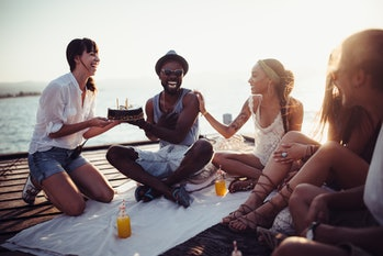 Young multi-ethnic hipster friends celebrating birthday with surprise birthday cake on wooden pier i...