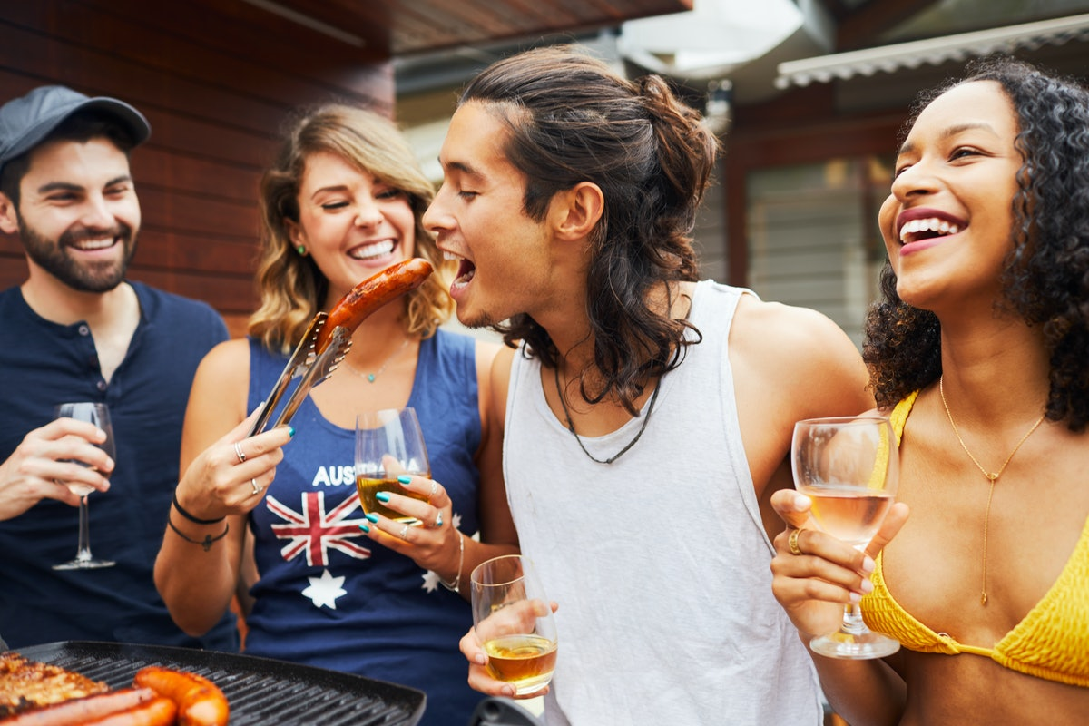 A group of friends plans a Summer 2021 Olympics watch party in their backyard, and laughs while eating hot dogs and attending the gathering.
