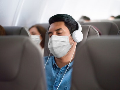 Portrait of a Latin American man traveling and sleeping on the plane wearing a facemask during the C...