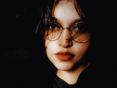 Young woman with glasses facing the camera, waiting to hear her August 2021 monthly horoscope.