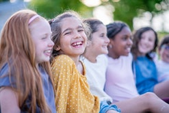A group of elementary age children around ten years old are hanging out together outdoors. The focus...