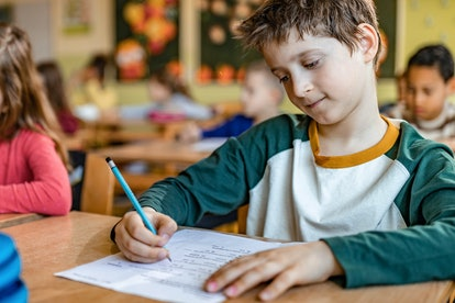 Schoolboy writing on a paper on his desk in the classroom.