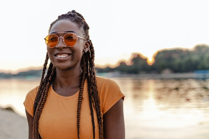Young African American woman is on outdoors, she is smiling