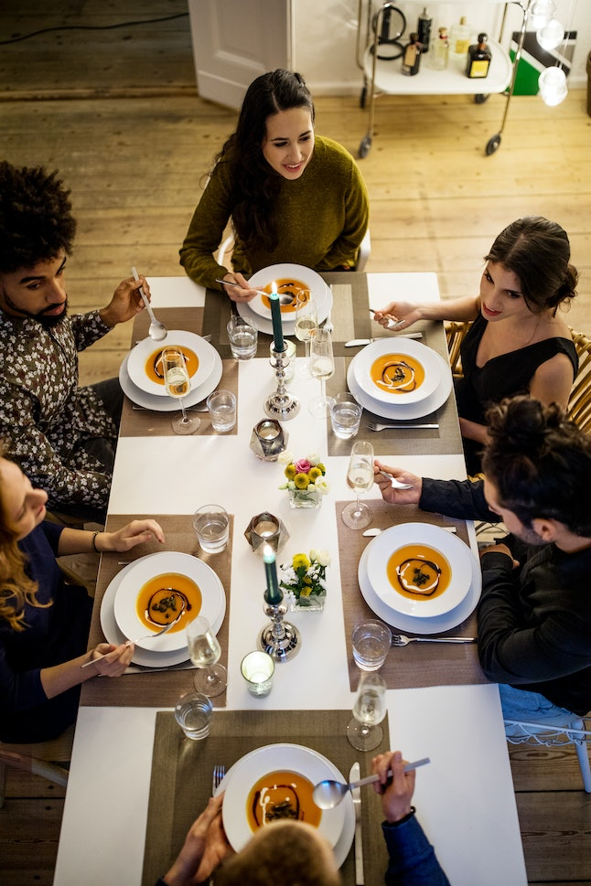 High angle view of multi-ethnic friends having squash soup at dinning table