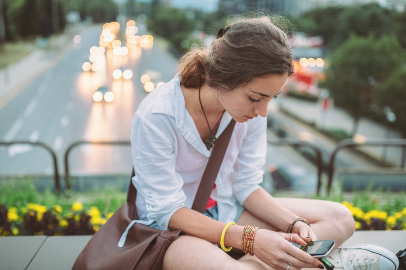 A person sits outside looking down at their phone. It's OK to text someone that you don't actually want a second date.