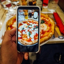 A man is taking a photo of his pizza in a restaurant in Naples, Italy. Searching Instagram locations can help you find new places to eat or sus out the vibe at a public spot.