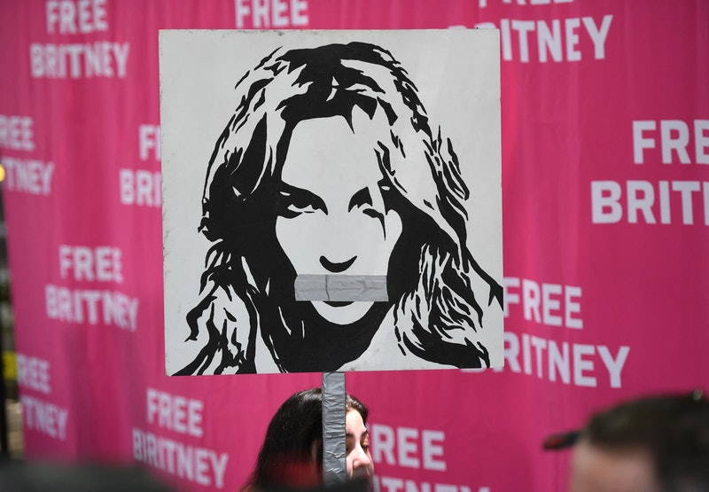 """A woman holds a poster of Britney with her mouth taped shut as fans and supporters gather outside the Los Angeles County Courthouse in Los Angeles on July 14, 2021, during a scheduled hearing in the Britney Spears guardianship case. - Three weeks after Britney Spears sensationally called for an end to her """"abusive"""" guardianship, the pop singer's legal battle returns to court July 14 in Los Angeles. Spears gave explosive testimony on June 23 in which she pleaded with a California judge to allow her to end the conservatorship long controlled by her father, and to choose her own lawyer. (Photo by Robyn Beck / AFP) (Photo by ROBYN BECK/AFP via Getty Images)"""