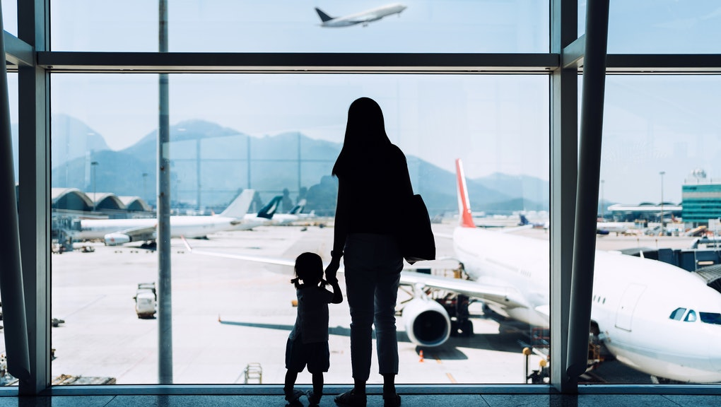 Silhouette of joyful young Asian mother holding hands with cute little daughter looking at airplane ...