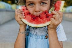 Little boy eating a piece of watermelon outdoors