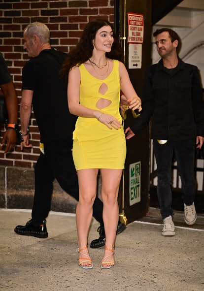 New Zealand singer and artist Lorde attends The Late Show with Stephen Colbert at the Ed Sullivan Theater on July 13, 2021, while wearing a yellow cutout mini dress that's so on-trend.