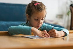 Little girl coloring with crayon in the living room