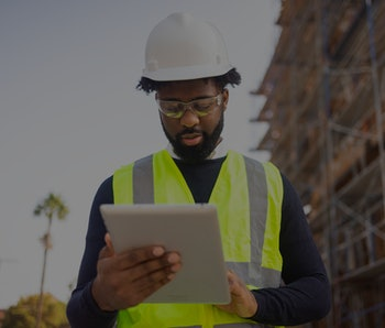 A young black man is a project manager at a residential construction site.